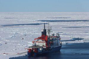 Polarstern liegt während der Driftstation an einer Scholle. Auf der Backbordseite markieren verschiedene Installationen und Flaggen die unterschiedlichen Messpunkte auf und unter dem Meereis. Foto: Svenja Kohnemann.
