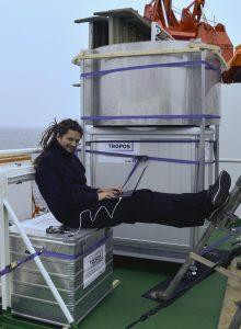 Hannes Griesche vom TROPOS vor dem Wolkenradar. In dem Schrank befindet sich eine Stabilisierungsplattform, welche die Schiffsbewegungen ausgleicht, so dass das Radar jederzeit senkrecht in den Himmel schaut. Foto: Carola Barrientos, TROPOS